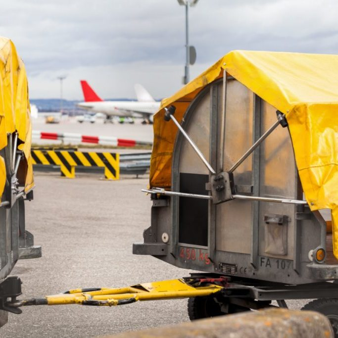 Trolleys loaded with luggage at an airport standing on the tarmac under yellow tarpaulins waiting to be loaded on an airplane